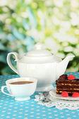 Theepot, kopje thee en heerlijke taart op natuurlijke achtergrond — Stockfoto