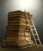 Old books and wooden ladder, on grey background — Stok fotoğraf