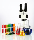 Test tubes with colorful liquids and microscope isolated on white — Stockfoto