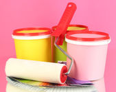 Set for painting: paint pots, paint-roller, palette of colors on pink background — Stock Photo