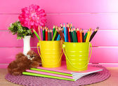 Colorful pencils in pails with copybooks and bear on table on pink background — Stock Photo