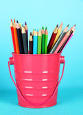 Colorful pencils in pail on blue background — Stock Photo