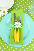 Knife and fork wrapped in napkin, on plate, on color tablecloth background — Stock Photo