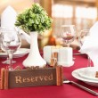 Reserved sign on restaurant table with empty dishes and glasses — Stock Photo #22385481