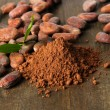 Cocoa beans and cocoa powder on wooden background — Stock Photo #22385801