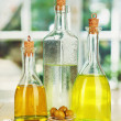 Original glass bottles with salad dressing on wooden table on window background - Stockfoto