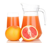 Full glass and jug of grapefruit juice and grapefruits isolated on white — Stock Photo