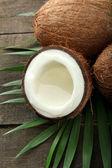 Noix de coco avec feuilles, sur un fond en bois gris — Photo