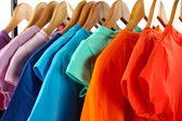 Escolha roupas de cores diferentes em cabides de madeira, isolados no branco — Foto Stock