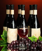 Composition of wine bottles, glass and grape, on dark red background — Stock Photo
