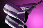 Hair dryer on purple background — Stock Photo