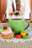 Cup of tea with cake and candy on table in room — Stock Photo