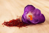Beautiful purple crocus and saffron, on wooden background — Stock Photo