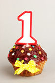 Birthday cupcake with chocolate frosting on grey background — Stock Photo