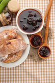 Taste croissants on plate and jam on tableclot — Stock Photo