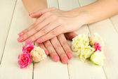 Woman hands with pink manicure and flowers, on wooden background — Photo
