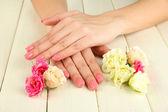 žena ruce s růžovými manikúru a květiny, na dřevěné pozadí — Stock fotografie