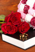 Wedding rings on bible with roses on wooden background — Foto de Stock