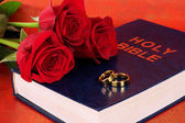 Wedding rings with roses on bible on red background — Stock Photo