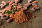 Cocoa beans and cocoa powder on wooden background — Stok fotoğraf