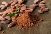 Fave di cacao e cacao in polvere sul fondo in legno — Foto Stock