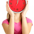Girl holding clock over face isolated on white — Stockfoto
