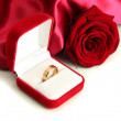 Beautiful box with wedding ring and rose on red silk background — Zdjęcie stockowe