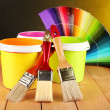 Paint pots, paintbrushes and coloured swatches on wooden table on dark yellow background — Stock Photo #22415397