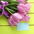 Stock Photo: Beautiful bouquet of purple tulips on green wooden background
