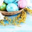 Easter eggs in basket and mimosa flowers, on blue wooden background — Stock Photo #22415665