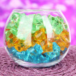 Glass with colorful decorative stones on bright background — Stock Photo