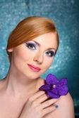 Krásná mladá žena s glamour make-upu a květin na modrém pozadí — Stock fotografie