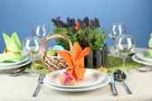 Easter table setting on color background — Zdjęcie stockowe