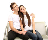 Young couple sitting together isolated on white — Stock Photo