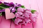 Beautiful bouquet of purple tulips on pink wooden background — Stok fotoğraf