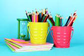 Colorful pencils with school supplies on blue background — Stock Photo