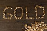 Or word avec des pierres dorées sur fond en bois — Photo