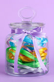 Glass jar containing various colored ribbons on lilac background — Stock Photo