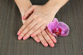 Woman hands with pink manicure and orchid on bamboo mat background — Zdjęcie stockowe