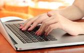 Vrouwelijke handen schrijven op laptop, op lichte achtergrond — Stockfoto