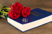 Wedding rings on bible with roses on wooden background — Stok fotoğraf