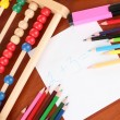 Stock Photo: Toy abacus, note paper, pencils on bright background