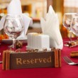 Reserved sign on restaurant table with empty dishes and glasses — Stock Photo #22475783