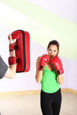 Young beautiful woman with boxing gloves at workout, at gym — Stock Photo
