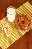 Bread roll and glass of milk on napkin on wooden table — Stock Photo