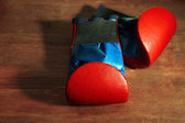 Small children boxing gloves on wooden background — Stock Photo