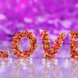 Word Love on purple background - Stock Photo