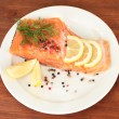 Fresh salmon fillet with herbals and lemon slices on plate,on wooden background - Stock Photo