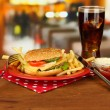 Tasty cheeseburger with fried potatoes and cold drink, on bright background — Foto de Stock