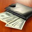 Wallet with hundred dollar banknotes, on wooden background — Stock Photo